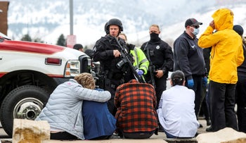 Police guard people evacuated after a call of an active shooter at the King Soopers grocery store in Boulder, Colorado.
