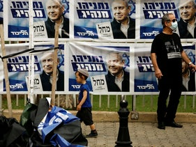 A young boy walks past Likud party election campaign banners depicting its leader Israeli Prime Minister Benjamin Netanyahu.