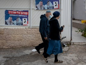 A religious couple walk past campaign posters for the United Torah Judaism party in Jerusalem's Har Nof neighborhood, Tuesday.