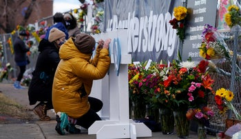 Mourners sign crosses placed in honor of the victims killed in the shooting in Boulder, Colorado.
