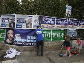 Campaign posters near a polling station in Tel Aviv, yesterday.