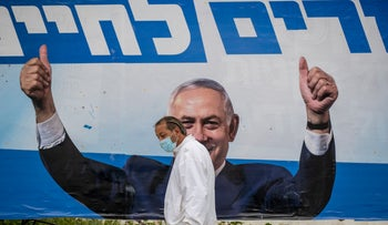 An Israeli man walks by a Netanyahu campaign poster in Jerusalem, this month.
