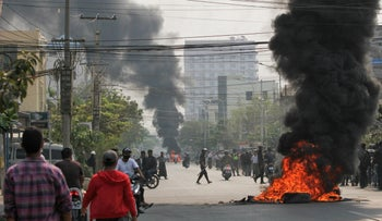 Tires burn on a street as protests against the military coup continue, in Mandalay, Myanmar, today.
