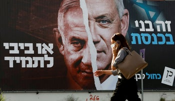 A woman walks past a Kahol Lavan campaign poster in Tel Aviv on Election Day, this month