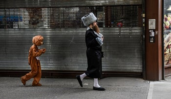 A man walks with his son who is dressed in a costume as people celebrate Purim in the Brooklyn borough of New York City, 2021.