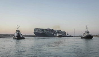 The Ever Given, a Panama-flagged cargo ship is pulled by tugboats, in the Suez Canal, Egypt, March 2021.