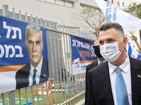 Gideon Sa'ar in Tel Aviv on Election Day with a campaign poster from Yair Lapid's Yesh Atid.