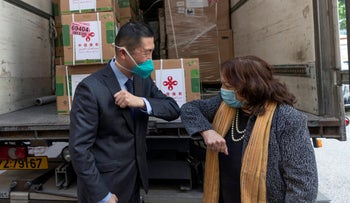 China's West Bank envoy Guo Wei bumps elbows with Palestinian Health Minister Mai Alkaila, while attending the delivery of a shipment of the Chinese Sinopharm vaccine in Ramallah on Monday.