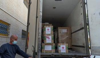 Workers prepare to unload a shipment of the Chinese Sinopharm vaccine in Ramallah on Monday.