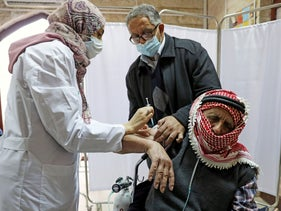A Palestinian man is helped by his son as he receives a vaccination against the coronavirus as Israel continues its national vaccination drive, in East Jerusalem late last year