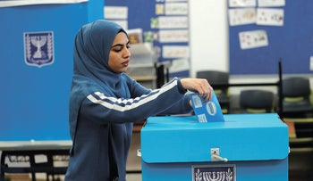 An Arab-Israeli woman casts her ballot as she votes in Israel's national election at a polling station in  Tamra