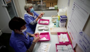 "Healthcare workers prepare intravenous doses of the ""Comirnaty"" Pfizer vaccine at South Ile-de-France Hospital Group in Melun, France."