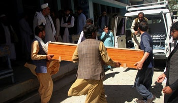 Afghans carry the body of a woman who was killed by gunmen in the city of Jalalabad, east of Kabul, Afghanistan.