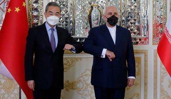 Iranian Foreign Minister Mohammad Javad Zarif (R) greets his Chinese counterpart Wang Yi, in the capital Tehran, on March 27, 2021