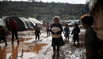 Syrian refugees walk through a camp for displaced people muddied by recent rains, near the village of Kafr Aruq, in Idlib province, Syria.