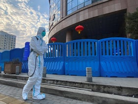 A worker in protective overalls walks outside the Wuhan Central Hospital where a whistleblower doctor who sounded the alarm and was reprimanded by local police for it in the early days of Wuhan's pandemic