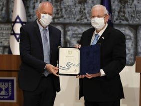 Central Election Committee chairman Uzi Vogelman hands the results to President Reuven Rivlin, today