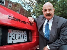 In this Monday, June 9, 1997, file photo, G. Gordon Liddy kneels next to his Corvette outside the Fairfax, Va., radio station where he broadcasts his syndicated radio talk show