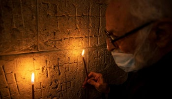 Father Samuel Aghoyan, the Armenian superior at the Church of the Holy Sepulchre holds candles to illuminate crosses etched into the ancient stone wall of the Saint Helena chapel inside the church, during his interview with Reuters, in Jerusalem's Old City