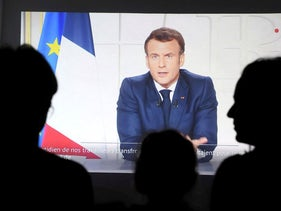 People listen to French president Emmanuel Macron delivering a broadcast speech from the Elysee palace in Paris, in Marseille