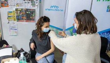 A patient receives the Pfizer vaccine from the Clalit HMO, last week.