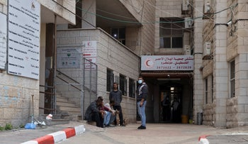 Men waiting outside a hospital in the Palestinian town of Tul Karm as relatives with COVID-19 are treated inside, Tuesday.
