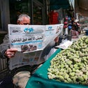 Jordanian street vendor reads a local newspaper with a headline on its front page about the latest events in his country, in the capital Amman, on April 4, 2021