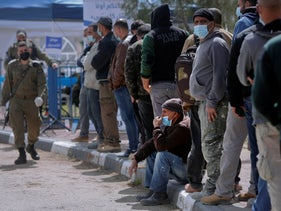 Palestinians who work in Israel line up at a coronavirus vaccination center set up at a crossing between Jerusalem and Bethlehem, last month.