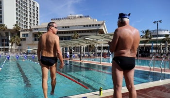 """Two Israeli men at a swimming pool next to the beach in Tel Aviv, only accessible to those with """"green passports."""""""