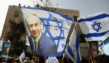 Supporters of Israeli Prime Minister Benjamin Netanyahu, wave an Israeli flag with an image of him, April 2021.