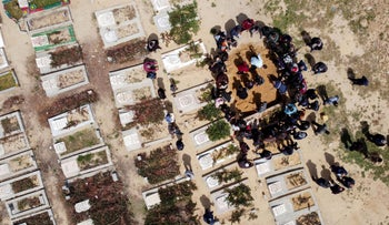 Palestinians burying the body of a man, who died after contracting the coronavirus, yesterday.