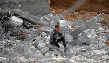 A Palestinian youth sits on the rubble of his family house that was demolished by Israeli forces, in Jordan Valley in the Israeli-occupied West Bank