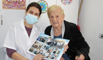 Debora Wanner, left, and Haifa Home resident Fanny Zelekovic last month, looking through a photo album of Zelekovic's 90th birthday party.