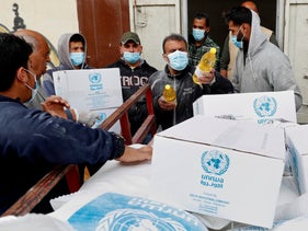 Palestinian workers load food supplies distributed by the United Nations Relief and Works Agency (UNRWA) in Gaza, 2020.