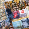 A bookshop owner sorts books at her shop. Storytel, a Swedish company, wants to make Hebrew audio books a thing in Israel