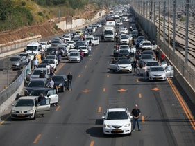 Cars stop on the sides of a highway as Israelis stand during a two-minute remembrance siren, in Tel Aviv, today.