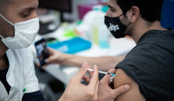 Israelis receive the COVID-19 vaccine at a vaccination center in Tel Aviv, this year.