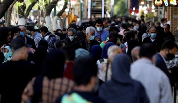 Iranians wearing protective face masks against the coronavirus walk in a crowded area of the capital Tehran, Iran, last month.