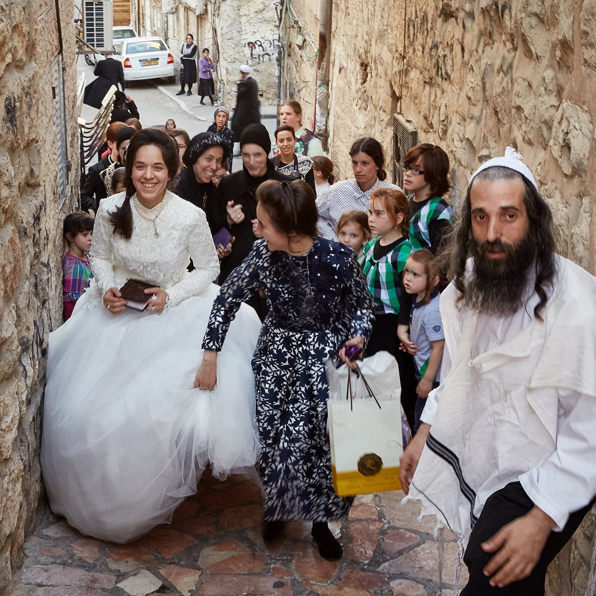 An ultra-Orthodox bride walking through a narrow alleyway.