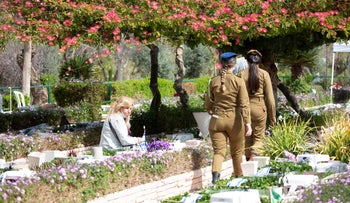 A woman at the tomb of a loved one at Kiryat Shaul cemetery, today