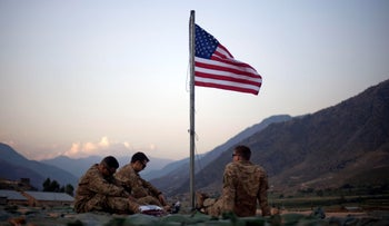 U.S. soldiers sit beneath an American flag just raised to commemorate the tenth anniversary of the 9/11 at Forward Operating Base Bostick in Kunar province, Afghanistan.