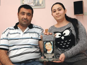 Eduard and Ilanit Yosepov at their home in Sderot.Ilanit is holding a picture of her late grandfather, Moredechai.