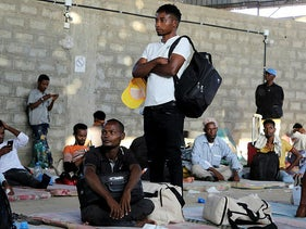 Ethiopian migrants rest before they were flown back to Ethiopia, at a UN-run shelter in Aden, on Tuesday.