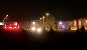 This image made from video shows a wide view of building with flashing lights from emergency vehicles in Indianapolis, IN