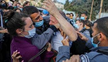 An Israeli policeman scuffles with Israeli MP Ofer Cassif (C), a Jewish member of the predominantly Arab Joint List electoral alliance, during a demonstration against Israeli occupation and settlement activity in the Palestinian Territories and east Jerusalem, April 9, 2021