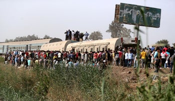 People gather at the site where train carriages derailed in Qalioubia province, north of Cairo, Egypt.