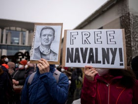 People show posters as they as they attend a protest against the jailing of Russian opposition leader Alexei Navalny, in front of the chancellery in Berlin, Germany.