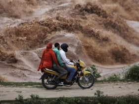 People riding on the banks of the River Tawi, flooded due to monsoon rains, in Jammu, India, 2012.