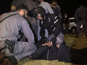 Police arrest a protester in Jaffa, yesterday.