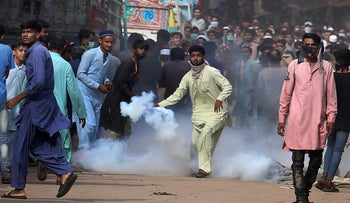 A supporters of Tehreek-e-Labiak Pakistan, a banned Islamist party, prepares to hurl back a tear gas canister fired by police to disperse protests, yesterday.